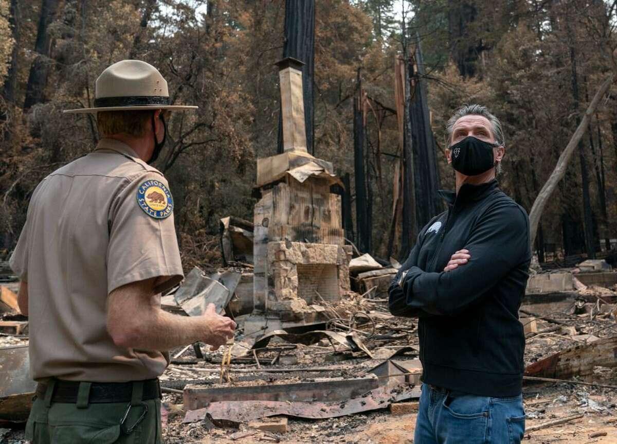 California Gov. Gavin Newsom listens as Santa Cruz State Park Superintendent Chris Spohrer discusses fire damage to Big Basin Redwoods State Park in Boulder Creek (Santa Cruz County) in September.