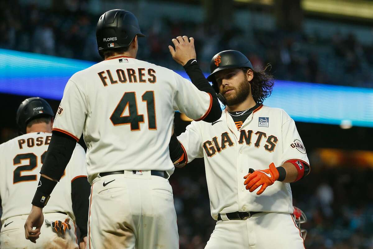 Giants shortstop Brandon Crawford celebrates with Buster Posey and Wilmer Flores after hitting a three-run home run in the bottom of the fifth inning against the Cubs at Oracle Park.