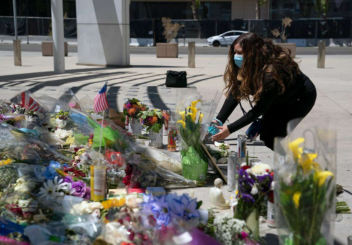 Valley Transportation Authority employee Gabby Ayala places a flower globe at a memorial for her fallen colleagues at San Jose City Hall on May 28.