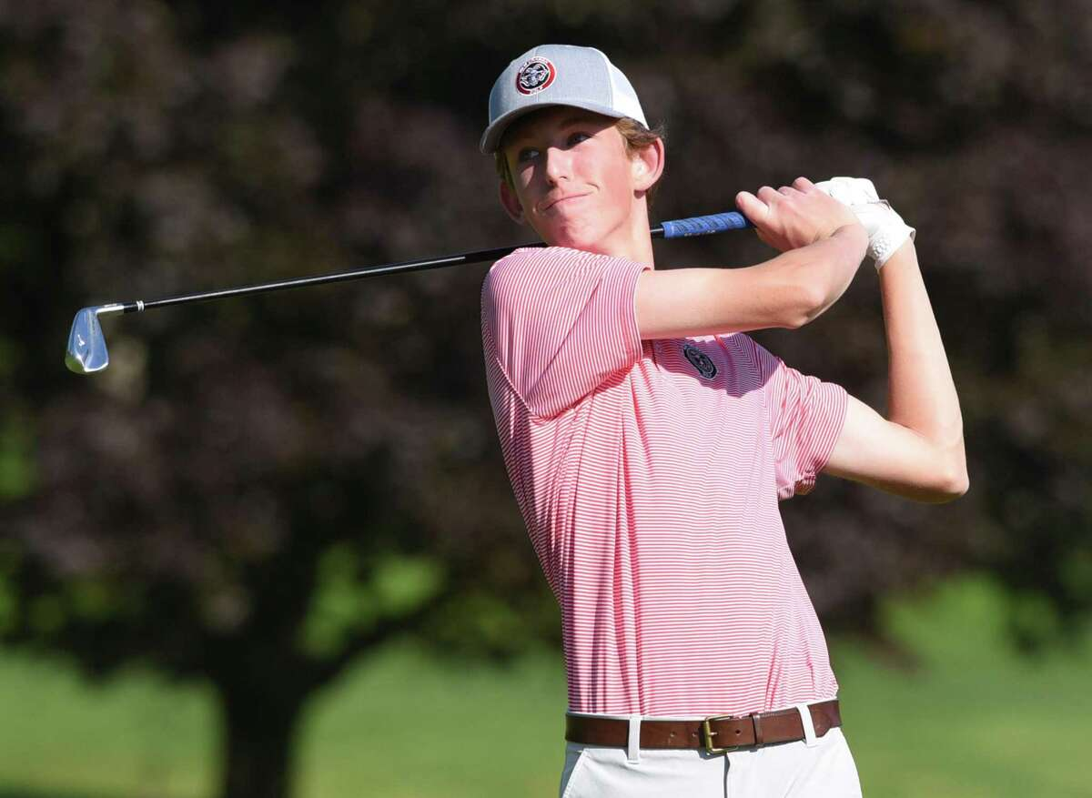 Sam Funk of the New Canaan boys golf team follows through during a match against Darien at the Wee Burn Country Club in Darien on Monday, May 17, 2021.