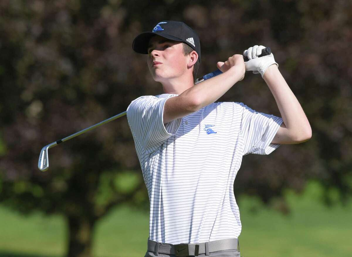 Thomas Ostberg of the Darien boys golf team follows the flight of the ball during a match against New Canaan at Wee Burn Country Club in Darien on Monday, May 17, 2021.