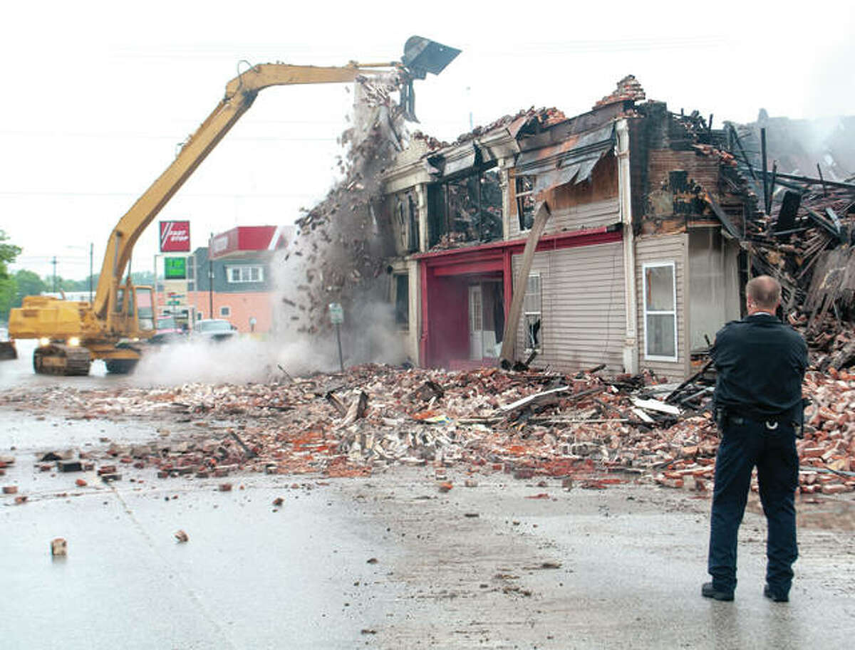 Beardstown Police Chief Martin Coad stands by May 17 as crews demolish the remains of the building at 601 E. Fourth St. after a fire swept through the evening before. Thirteen families were left homeless and three firefighters were injured.