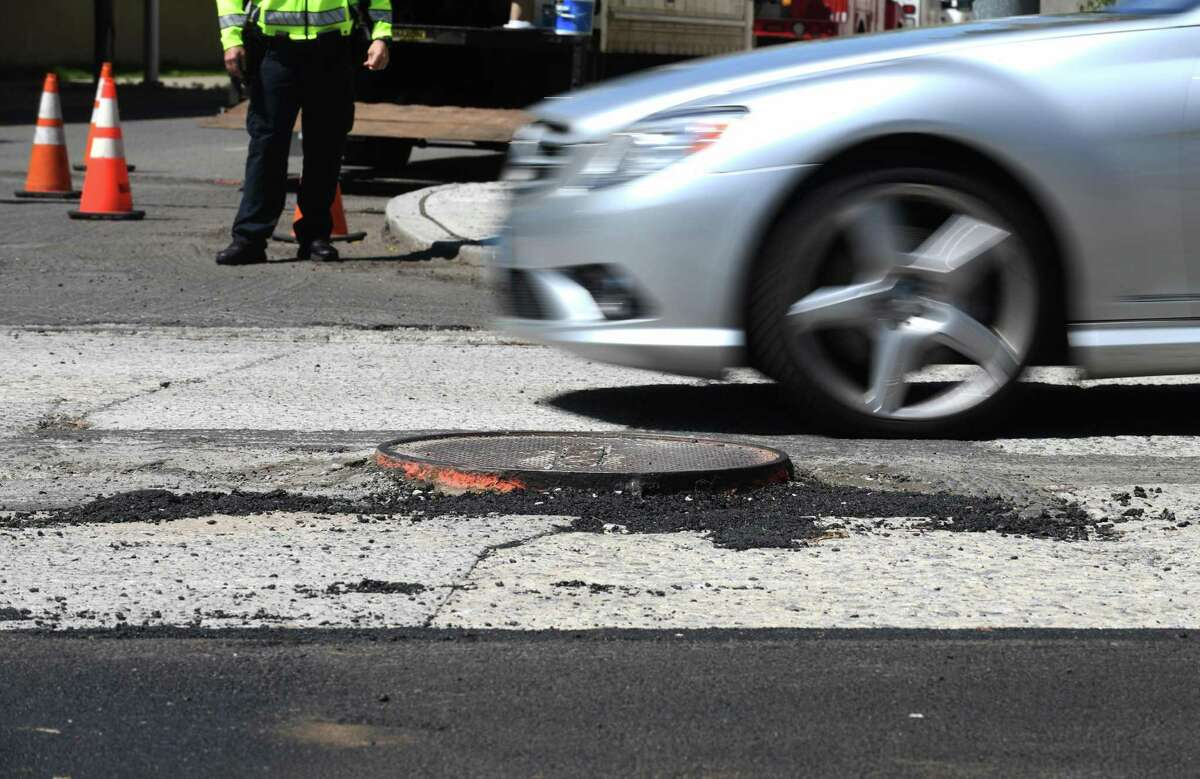 A car dodges a raised manhole cover during paving of Summer Street on May 6, 2021. Starting June 7, repaving of Washington Boulevard between Tresser Boulevard and High Ridge Road begins.