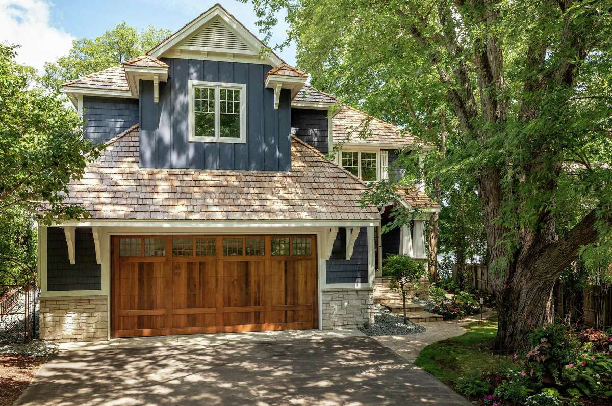 They swapped a three-car garage for a two-car garage and improved the home's curb appeal with a new, wood garage door and dark blue cedar shingles.