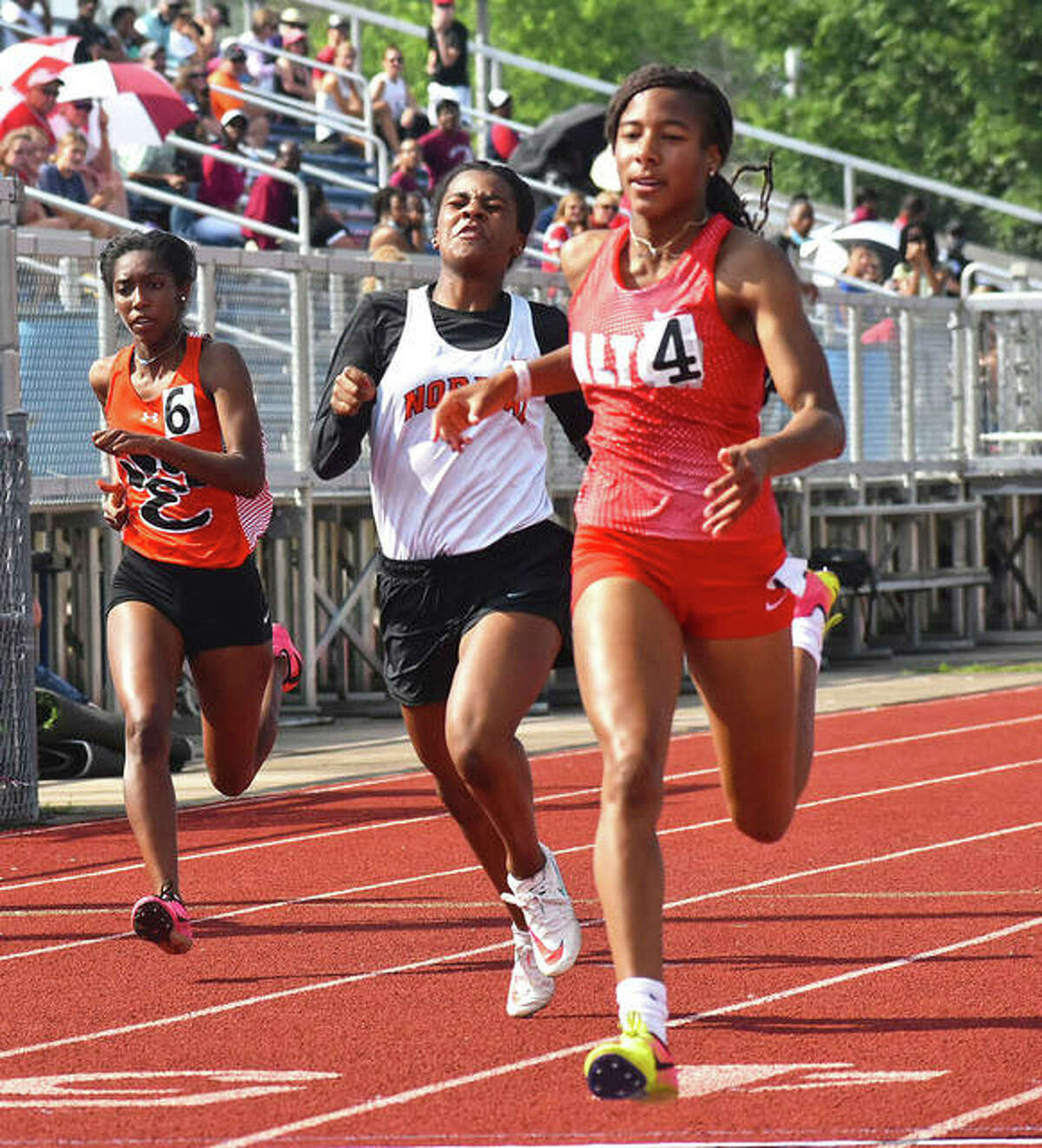 Alton's Renee Raglin (right) approaches the finish line Thursday at the O'Fallon Class 3A Sectional, where she won both the 100 and 200 meters to advance to the state meet in both events next week at Charleston.