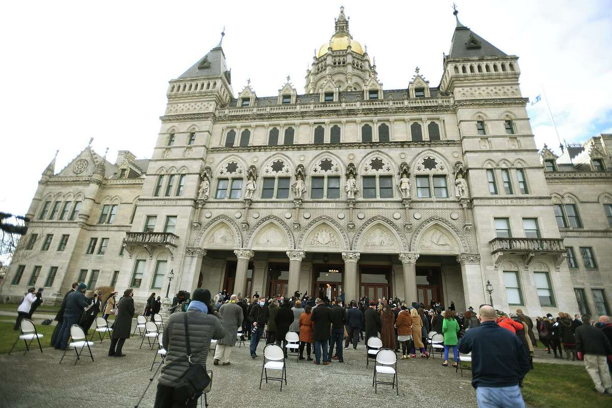 Representatives are sworn in outside the Capitol in Hartford, Conn. on Wednesday, January 6, 2021.