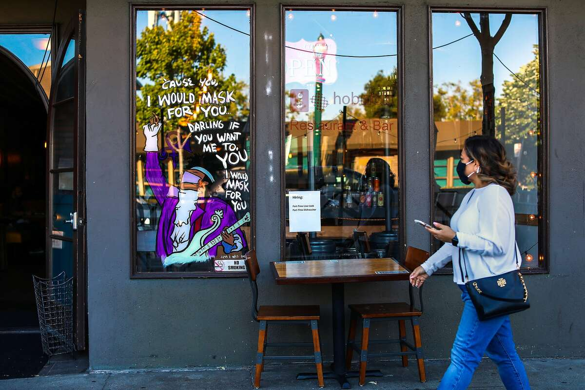 A woman passes by The Hobnob restaurant, which displays an image of the late artist Prince donning a mask, on Park St. on Thursday, June 3, 2021, in Alameda, Calif. For the last year we've become accustomed to slow streets, plexiglass screens at counters, social distancing stickers, you name it. Will they continue after June 15?