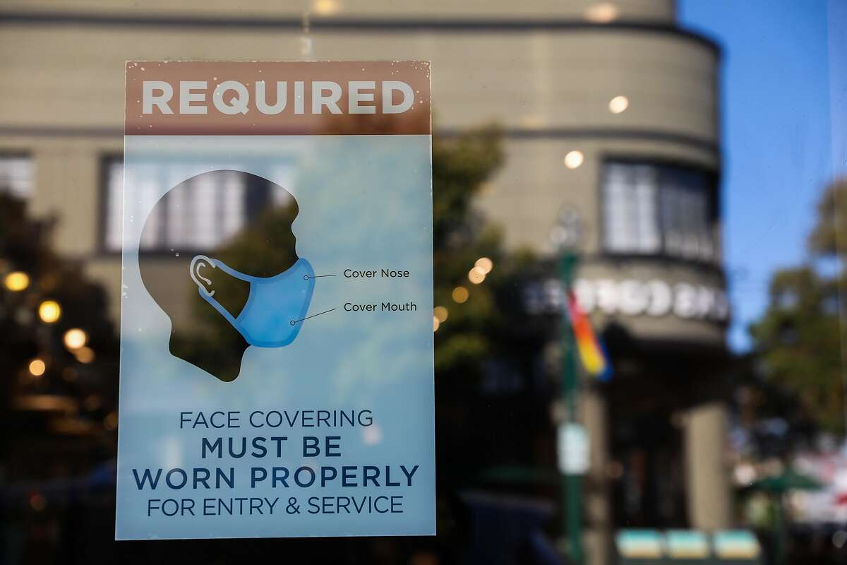 A poster detailing mask instructions is displayed at a business on Park St. on Thursday, June 3, 2021, in Alameda, Calif.