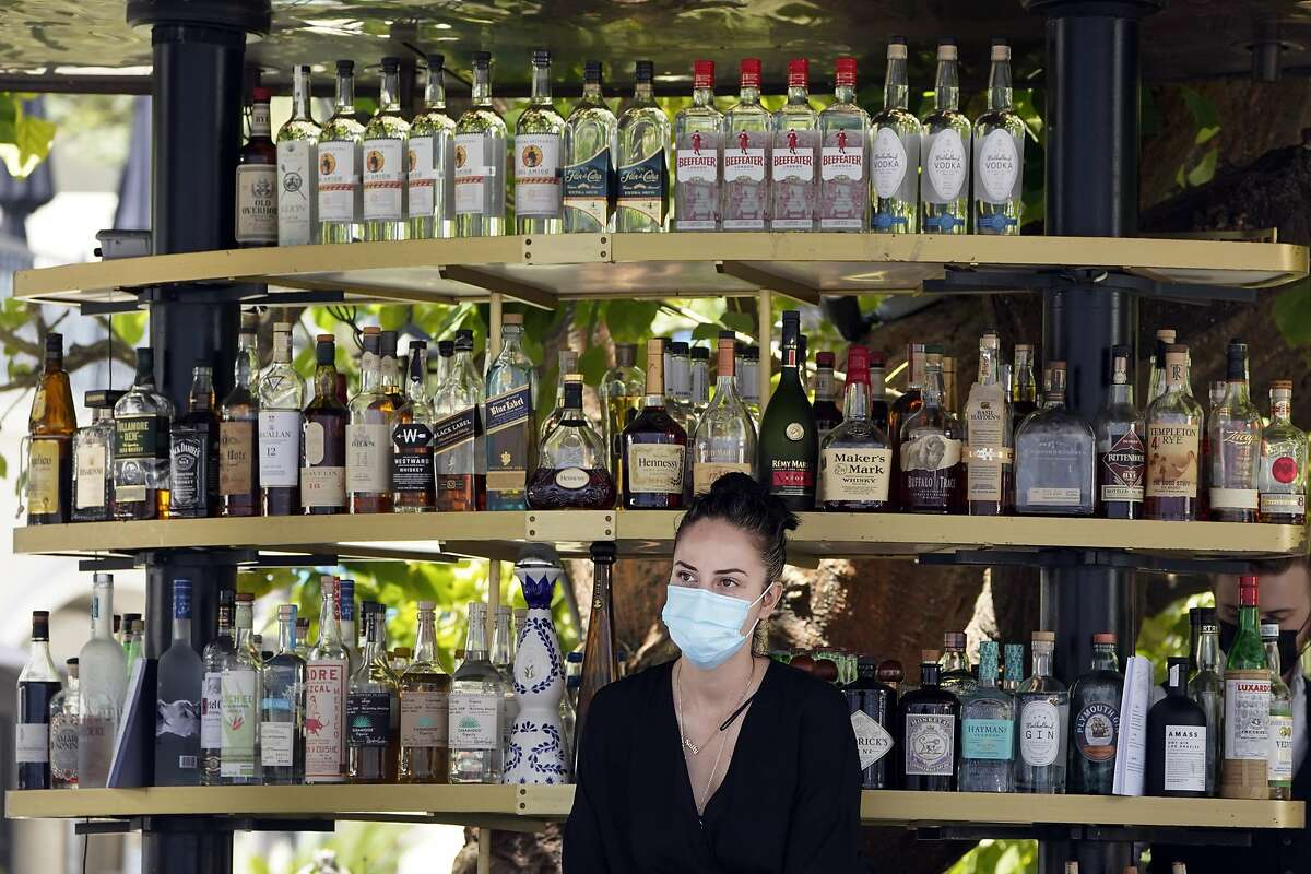 A bartender wears a mask while working at an outdoor bar at The Grove in Los Angeles. The standards board of California's Division of Occupational Safety and Health, voted to loosen workplace mask rules on Thursday, but the new standards are still more strict than the CDC's guidelines.