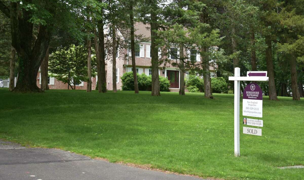 A Berkshire Hathaway HomeServices New England Properties sign declares a home sold set back from Ridgecrest Road in Stamford, Conn., in June 2021.