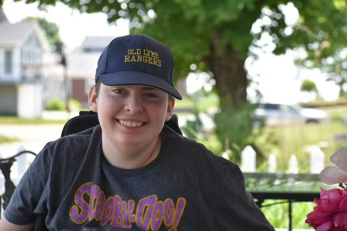 RJ Thomas of Southington, who has a rare genetic disease, sits on the front porch of the Hawks Nest Beach cottage in Old Lyme, where the family is staying for the next two weeks.