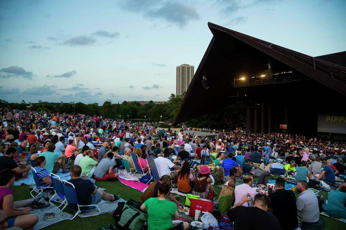 People grab seats on the lawn before a 2017 concert at the Miller Outdoor Theater.