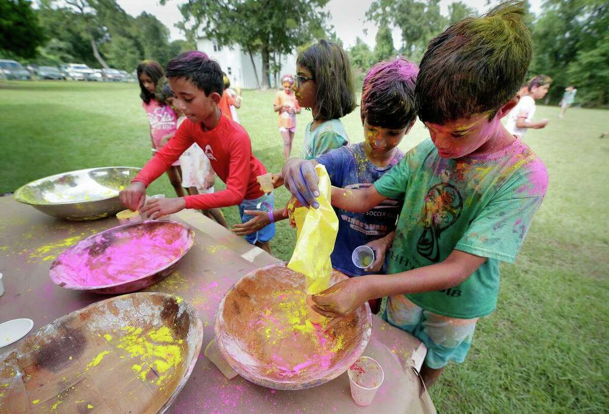 Elementary- and middle-school-aged campers, covered with colored powder, refill their cups during the Holi Festival celebration at the Hindu Heritage Youth Camp in 2019 at Camp Lantern Creek near Montgomery. Camp will resume in person this summer.