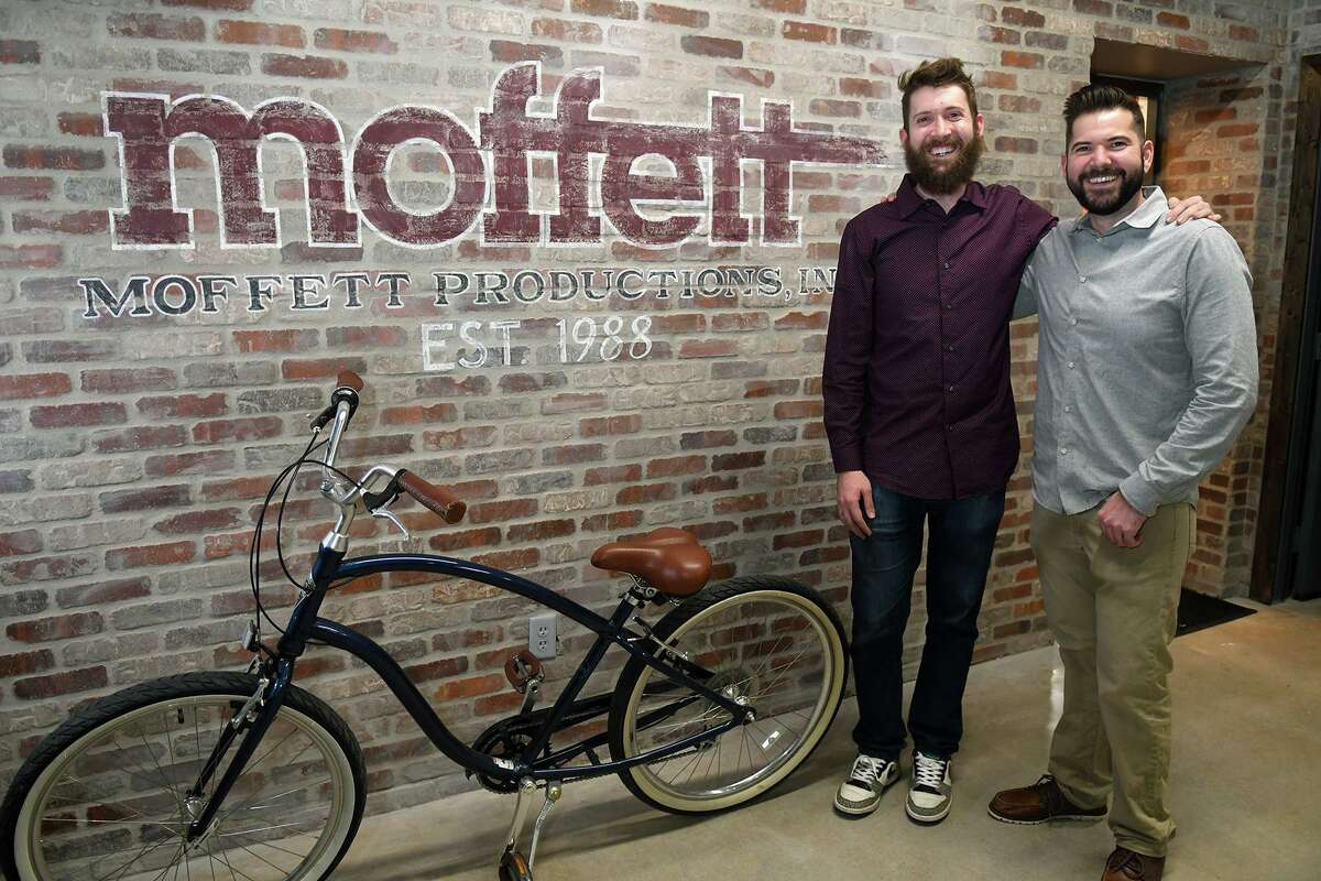 Chris Woher, left, and his brother Jeff, co-owners of Moffett Productions, share a photo in their new business during their grand opening in Tomball on Feb. 1, 2019.