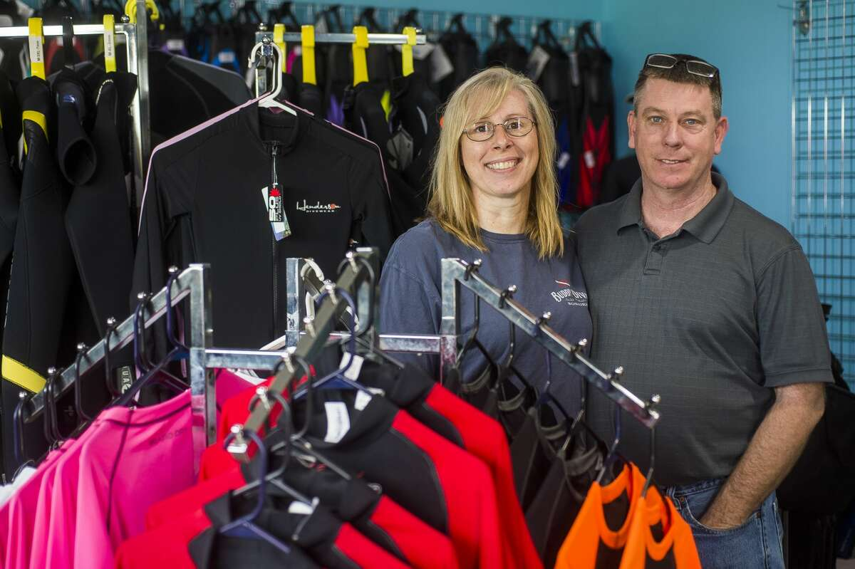 Underwater Antics co-owners Cheryl Roggenbuck, left, and Tim Middleton, right, pose for a portrait Friday, June 4, 2021 inside the Seaquatics shop at 4021 Isabella Road, which they recently purchased with the plan to combine the two businesses. (Katy Kildee/kkildee@mdn.net)