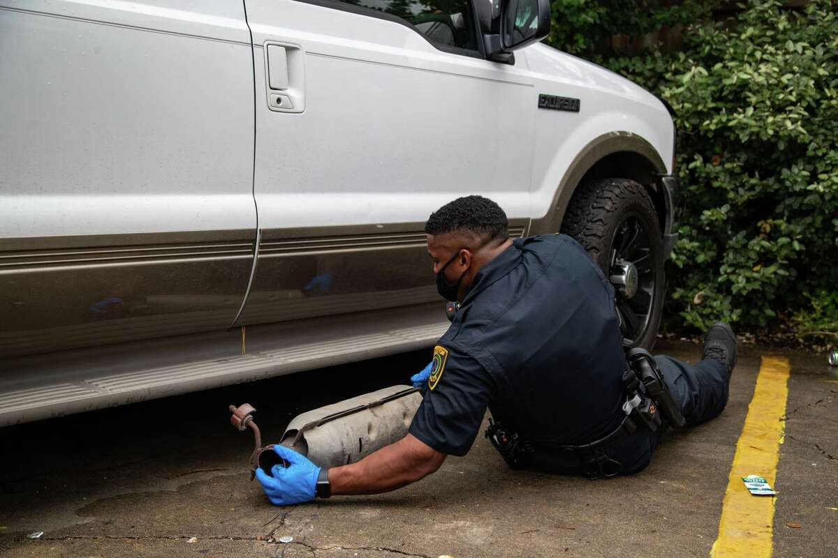 Houston Police Department officers pull out a stolen catalytic converter after checking under the vehicle as part of the investigation, Friday, June 4, 2021, in Houston.