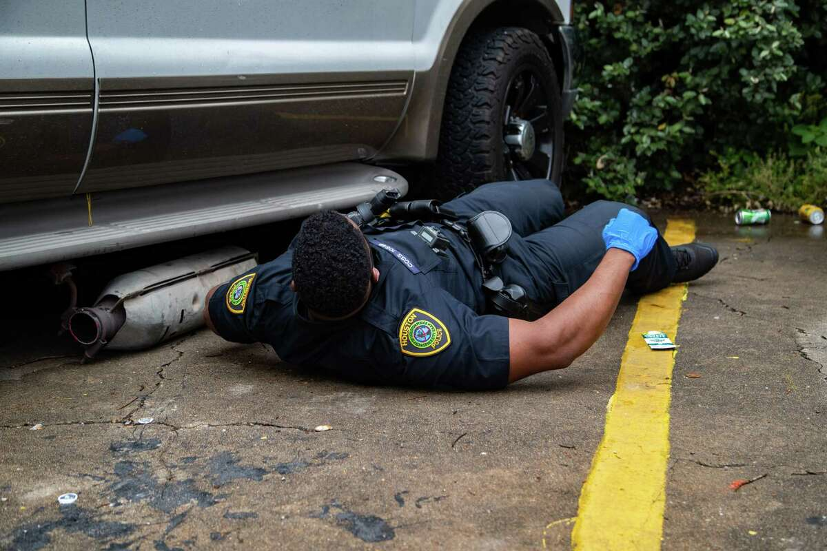 A Houston Police Department officer checks under the vehicle on which a catalytic converter had been stolen from as part of an investigation, Friday, June 4, 2021, in Houston.