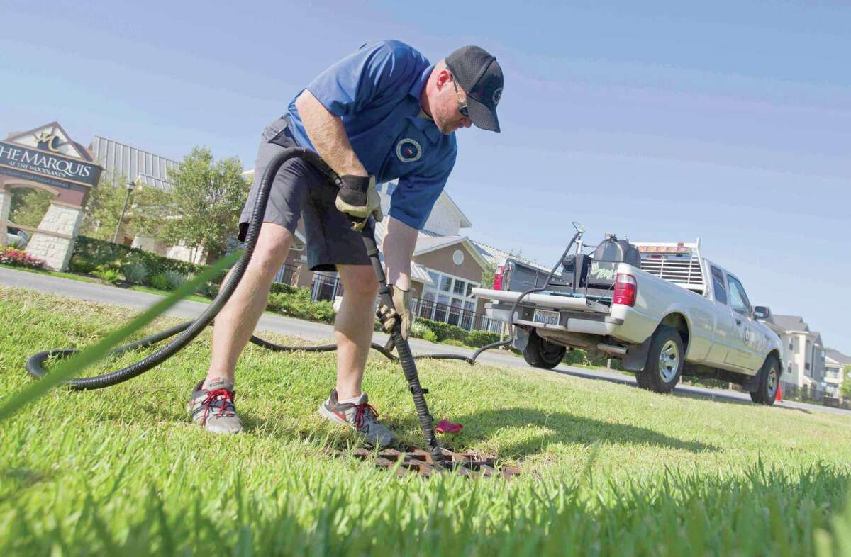 In this file photo, a crew member with Montgomery County Precinct 3 Office fumigates a drainage line for mosquitoes in The Woodlands.