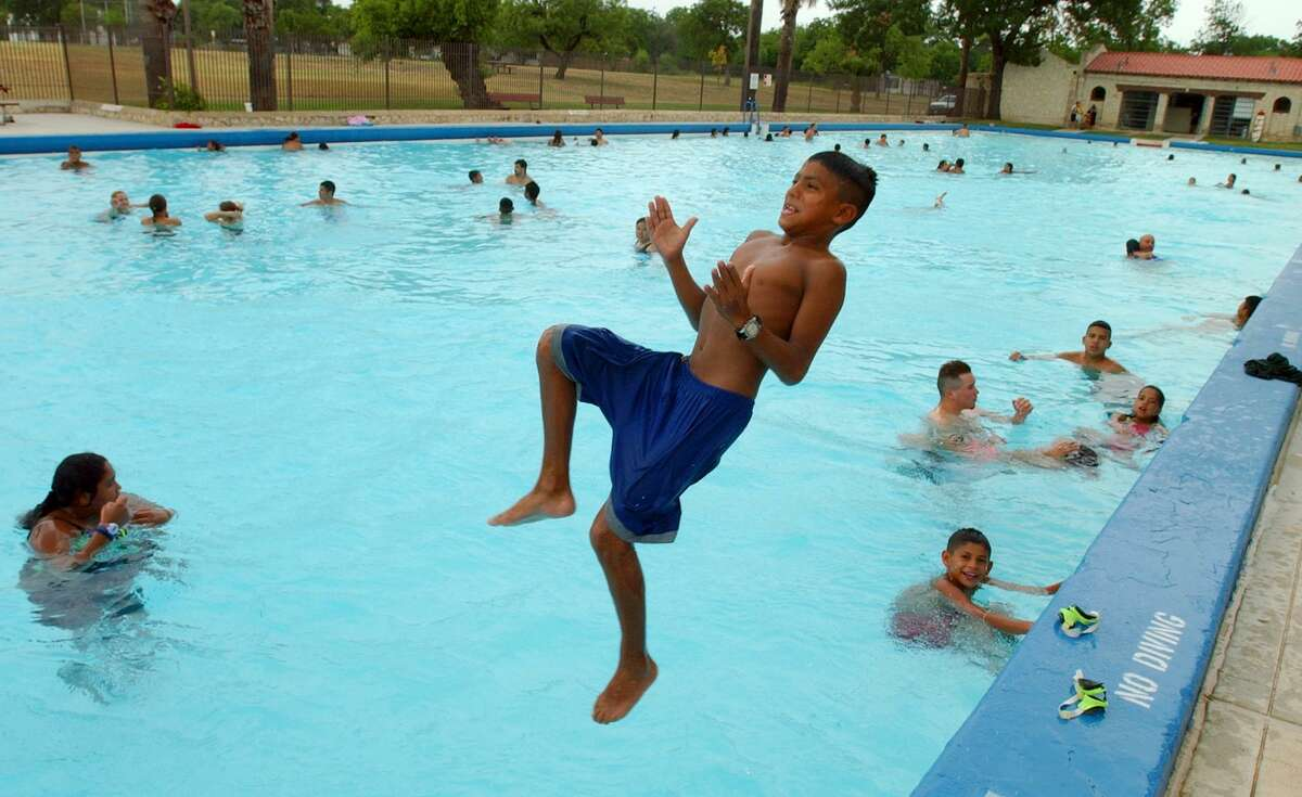 In this 2002 photo, John Obaya, 11, jumps into the swimming pool at Woodlawn Lake Park. The pool opened in 1925 and is the second-largest municipal pool in San Antonio.