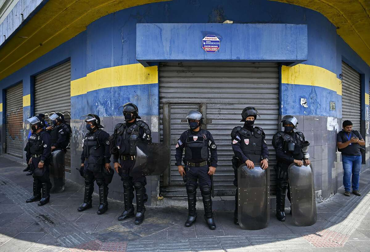 Anti-riot police stand guard outside shops and supermarkets in San Salvador in 2020 during a national protest.