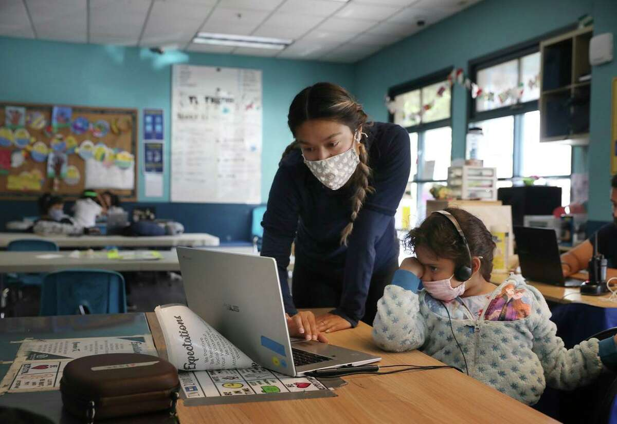 Desiree Almeida, health and fitness coordinator, works with Shaima at the elementary school learning hub at the Tenderloin Clubhouse campus in May. Masks are required for all in K-12 schools.