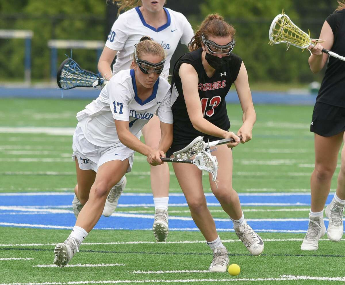 Darien's Ryan Hapgood (17) and Cheshire's Taryn Ugrin (13) battle for a groundball during their Class L quarterfinal game Friday.