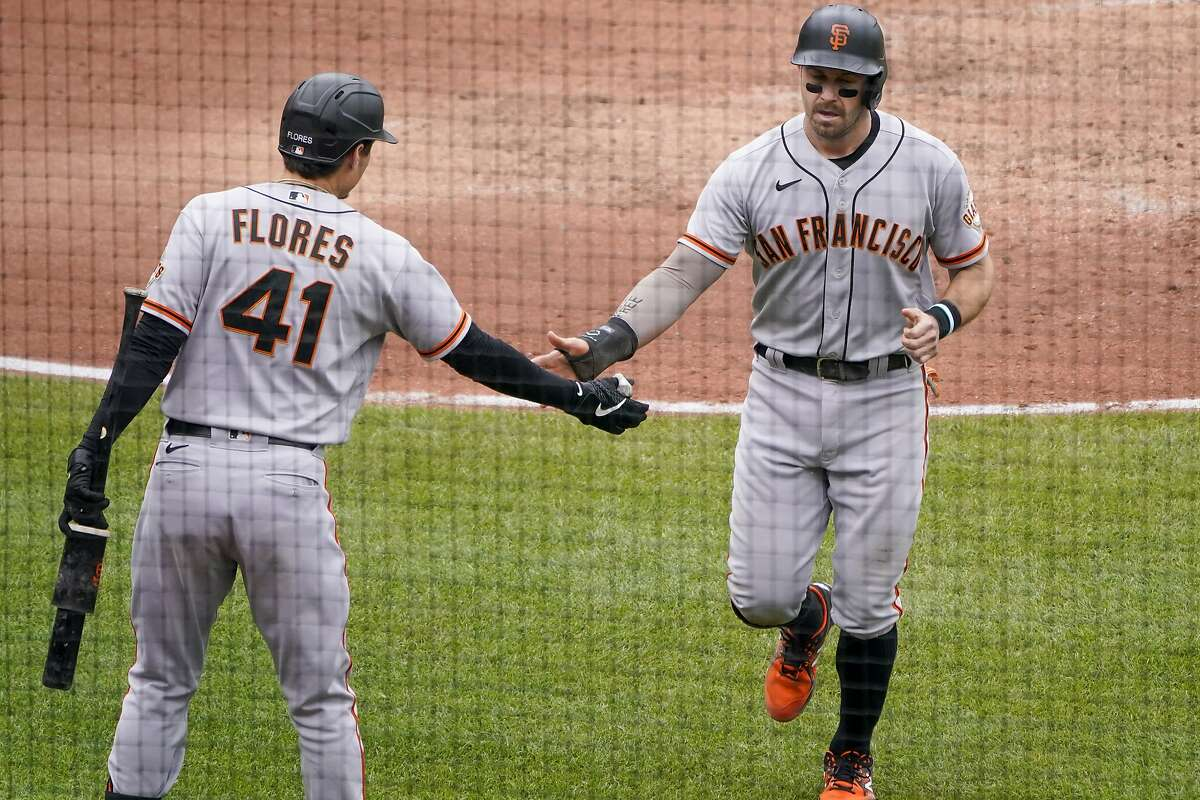 San Francisco Giants' Evan Longoria, right, is greeted by Wilmer Flores after he scored on a wild pitch by Pittsburgh Pirates relief pitcher Clay Holmes in the sixth inning of a baseball game, Sunday, May 16, 2021, in Pittsburgh.