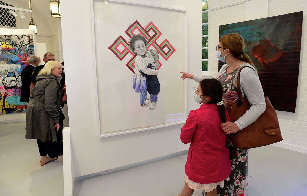 Local residents including Jennifer Katona and her daughter Sophie Katona, 9, look at the work of Duvian Montoya, United for Juastice, as they attend the grand opening reception for the Norwalk Art Space Friday, June 4, 2021, in Norwalk, Conn.