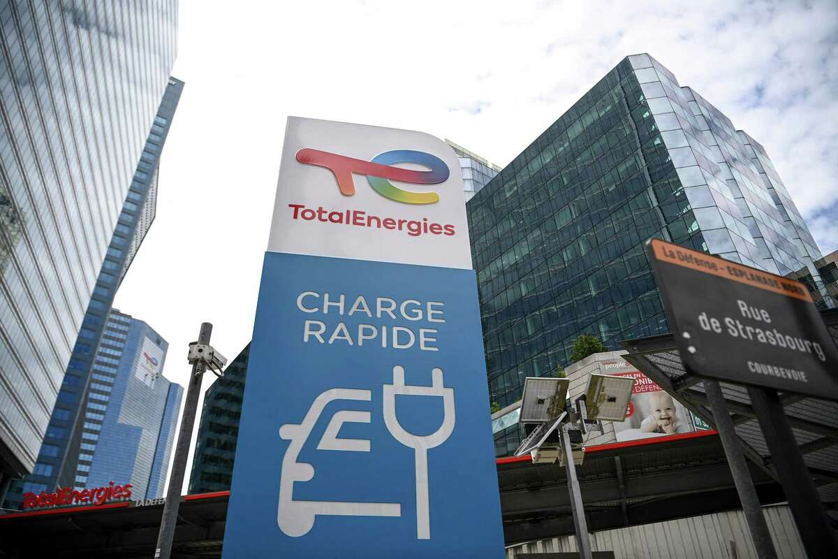 This photograph taken on May 28, 2021 shows the new TotalEnergies logo during its unveling ceremony, at a charging station in La Defense on the outskirts of Paris. - Total shareholders voted on the strategy of the oil and gas giant, which renamed itself TotalEnergies to mark its diversification, while some investors are urging it to act more quickly. (Photo by Christophe ARCHAMBAULT / AFP) (Photo by CHRISTOPHE ARCHAMBAULT/AFP via Getty Images)