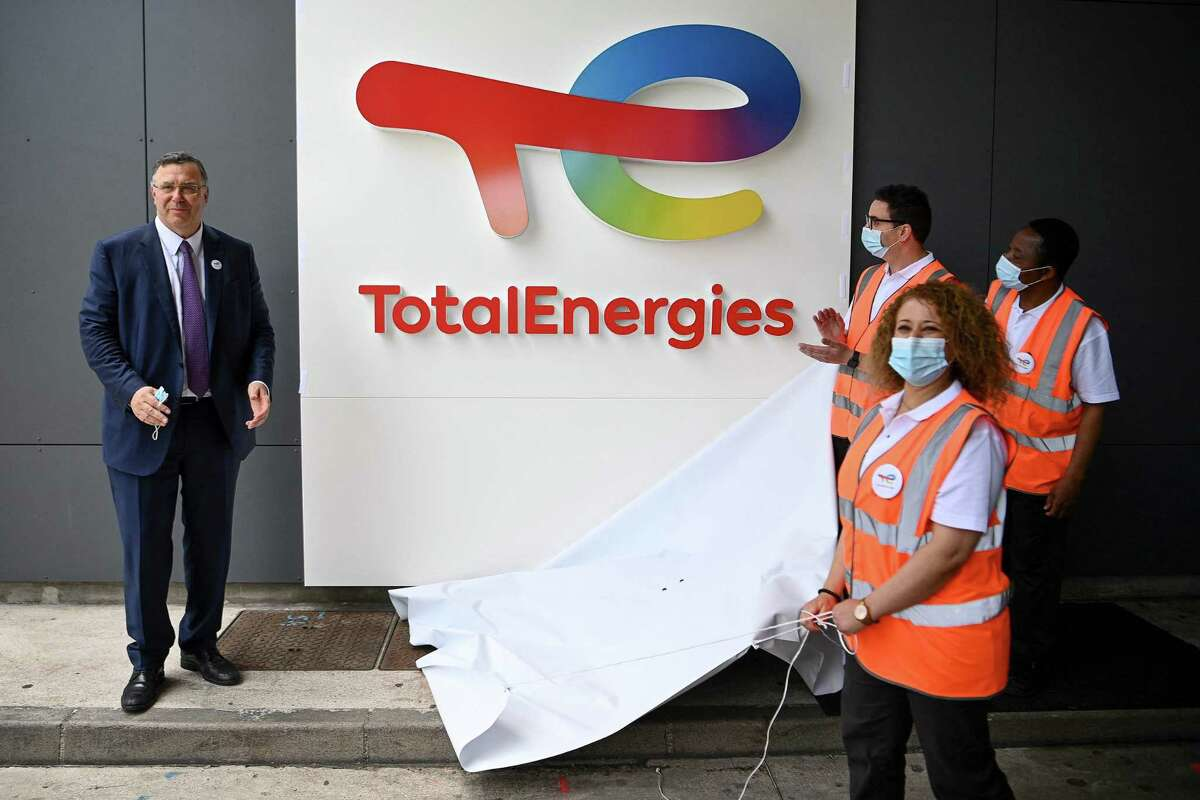 Total Chief Executive Officer Patrick Pouyanne (L) and Total employees remove a cover to reveal the new TotalEnergies logo during its unveiling ceremony, at La Defense on the outskirts of Paris on May 28, 2021. - Total shareholders voted on the strategy of the oil and gas giant, which renamed itself TotalEnergies to mark its diversification, while some investors are urging it to act more quickly. (Photo by Christophe ARCHAMBAULT / AFP) (Photo by CHRISTOPHE ARCHAMBAULT/AFP via Getty Images)