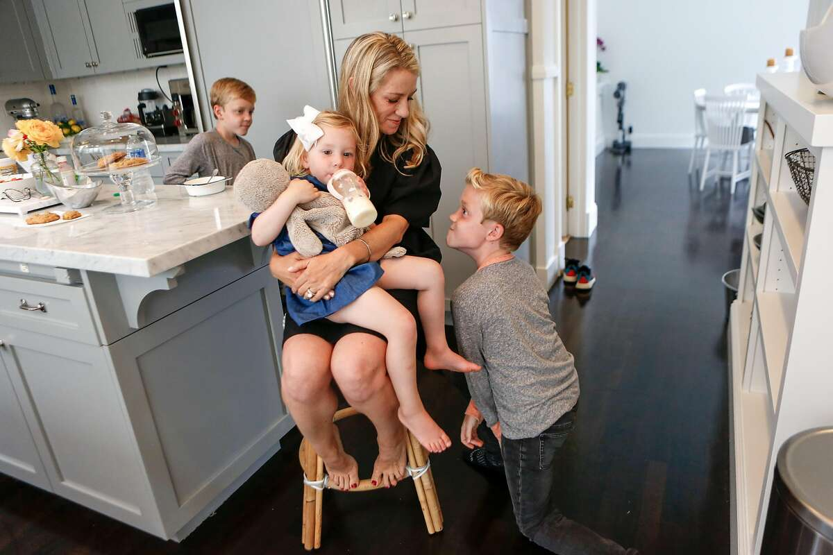 Dayna Quanbeck laughs as twin 10-year-old sons Elliott (left) and Ethan try to amuse their 2-year-old sister, Abigail.