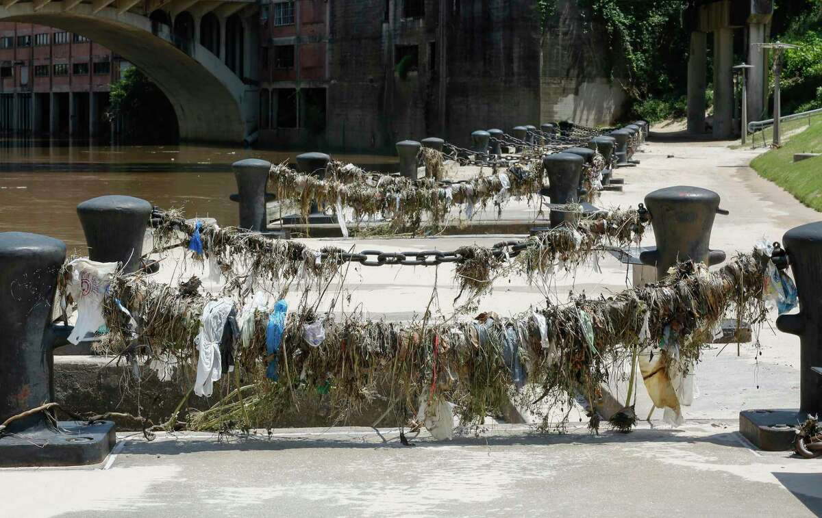 Plastic and other waste is visible along Buffalo Bayou in downtown Houston.