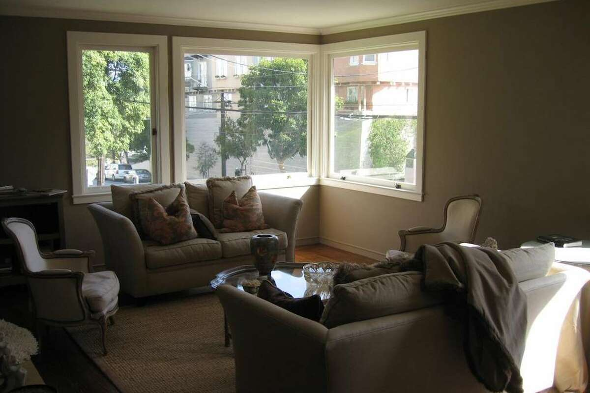 The unit is approximately 1,200 square feet, according to the listing, which is pretty sizable for a two-bedroom in the city. The living room has large corner windows, there are two bathrooms, and hardwood floors throughout.