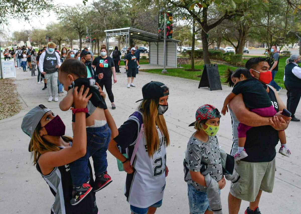 Holly Alvarado holds her little brother, Ryu, as they and the rest of the Alvarado family prepare to be the first to enter the AT&T Center for the team's