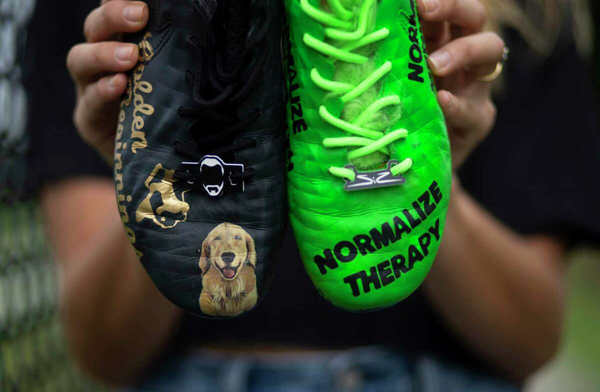 Houston Dash midfielder Gabby Seiler with a pair of custom-designed cleats with her messages,