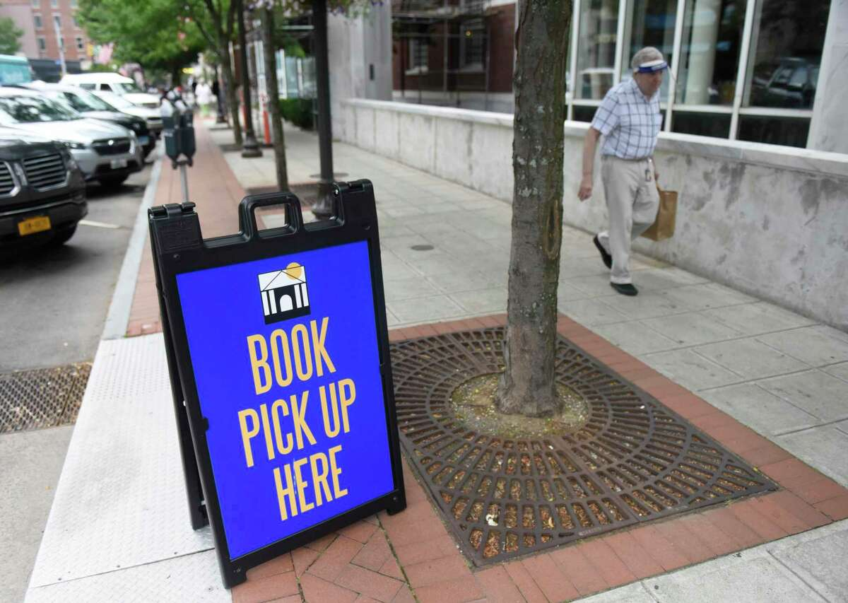 A sign indicates curbside pickup at Ferguson Library in Stamford, Conn. Tuesday, July 7, 2020.