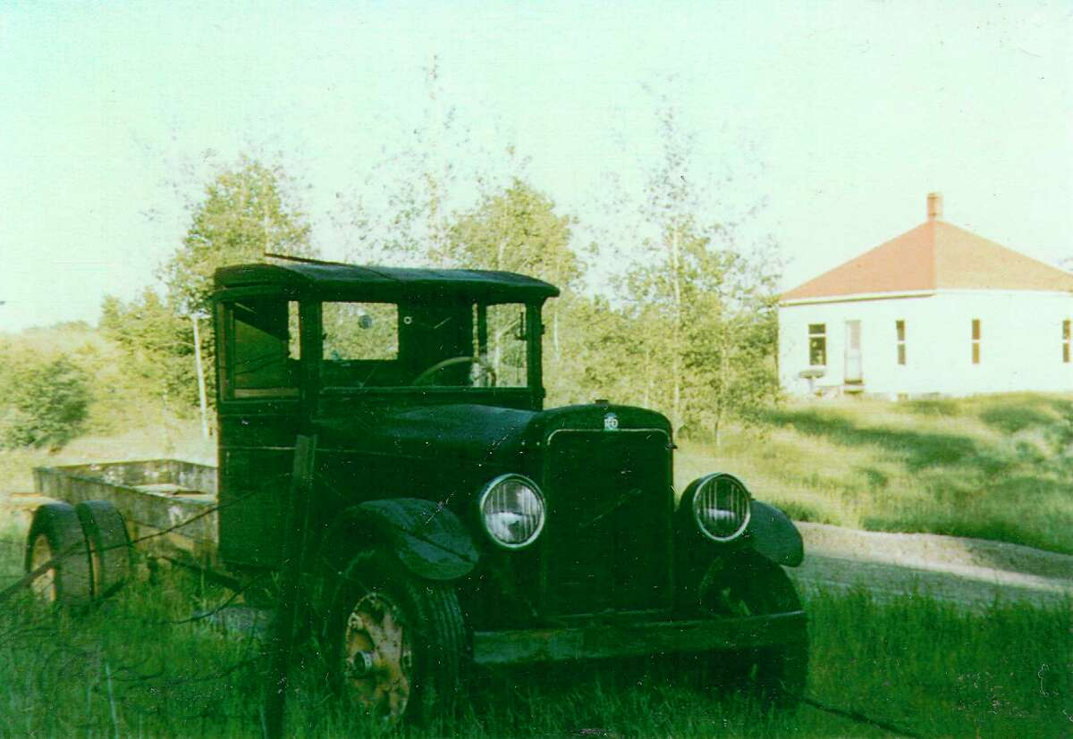 A Reo truck hauled many lugs of cherries to the Cherry Growers Cannery through the years for the Putney family farm north of Honor. The Putney house in the background was later moved to Dymond Orchards for tenant and later migrant housing. It still stands today on Dymond Road, and may have originally been moved from Averytown. (Courtesy Photo)