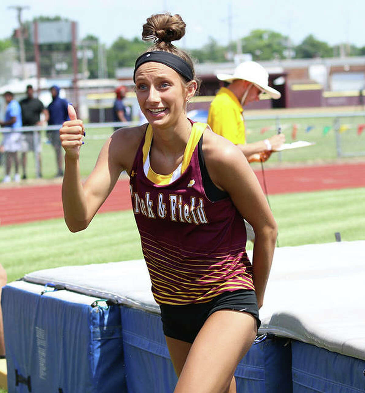 EA-WR's Hannah Sechrest gets off the pad gives a up thumbs up to her family watching from behind the fence after she cleared the state-qualifying height to earn her second state trip in the long jump on Friday at the Class 2A sectional in Wood River.