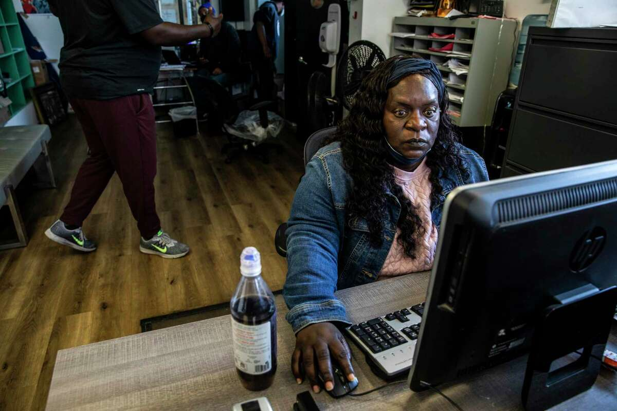 Arieann Harrison, center, works from her desk at United Council of Human Services in San Francisco, Calif., on Thursday, May 13, 2021. Her late mother used to work at the Hunters Point shipyard, where housing construction has embroiled the neighborhood in a years-long environmental battle.