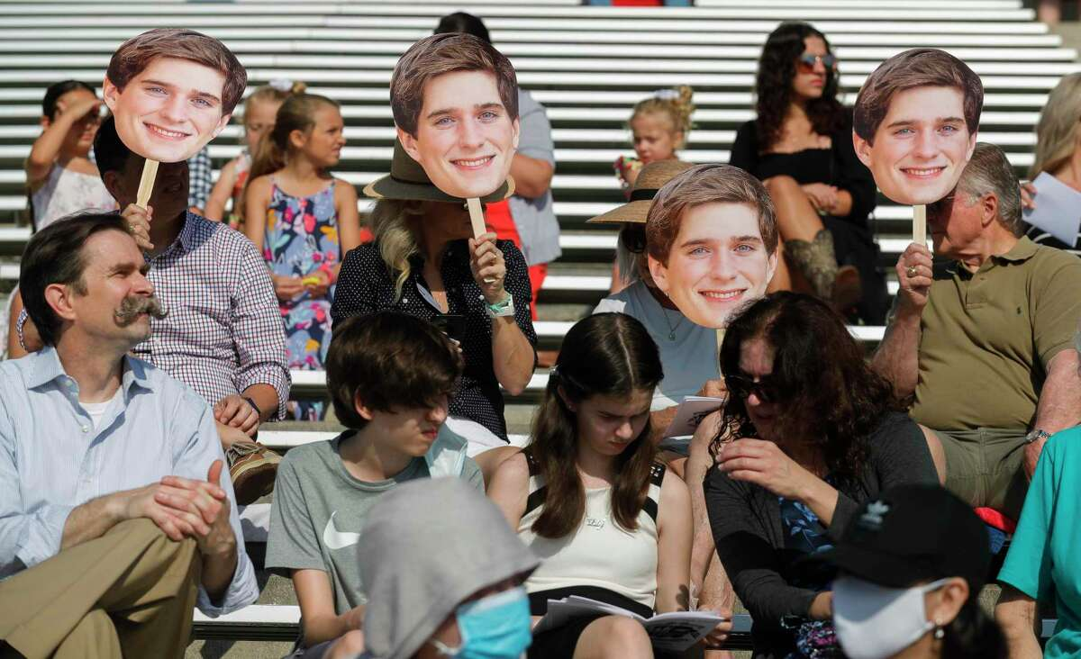Tanner Rios' family block the sun with cutouts of his face during a graduation ceremony for Kingwood High School at Turner Stadium, Thursday, June 3, 2021, in Humble.