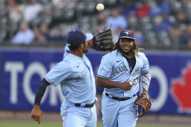 Toronto Blue Jays' Vladimir Guerrero Jr. (27) tosses the ball to Marcus Semien after making a catch for an out on Houston Astros' Carlos Correa during the third inning of a baseball game in Buffalo, N.Y., Friday, June 4, 2021. (AP Photo/Joshua Bessex) Photo: Joshua Bessex/Associated Press / Copyright 2021 The Associated Press. All rights reserved