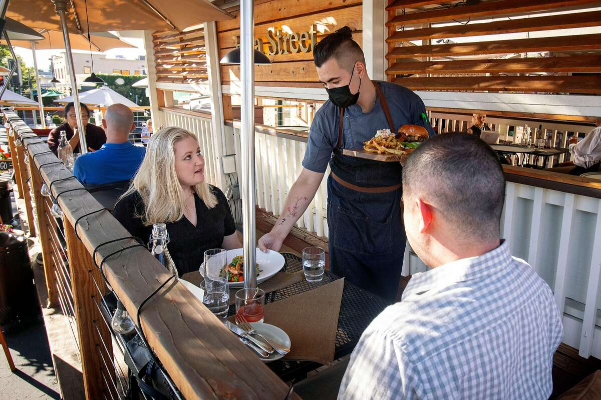Chef De Cuisine Bryan Thuerk at Menlo Park's Flea St. Cafe delivers plates to guests during dinner service on Wednesday, June 2, 2021.