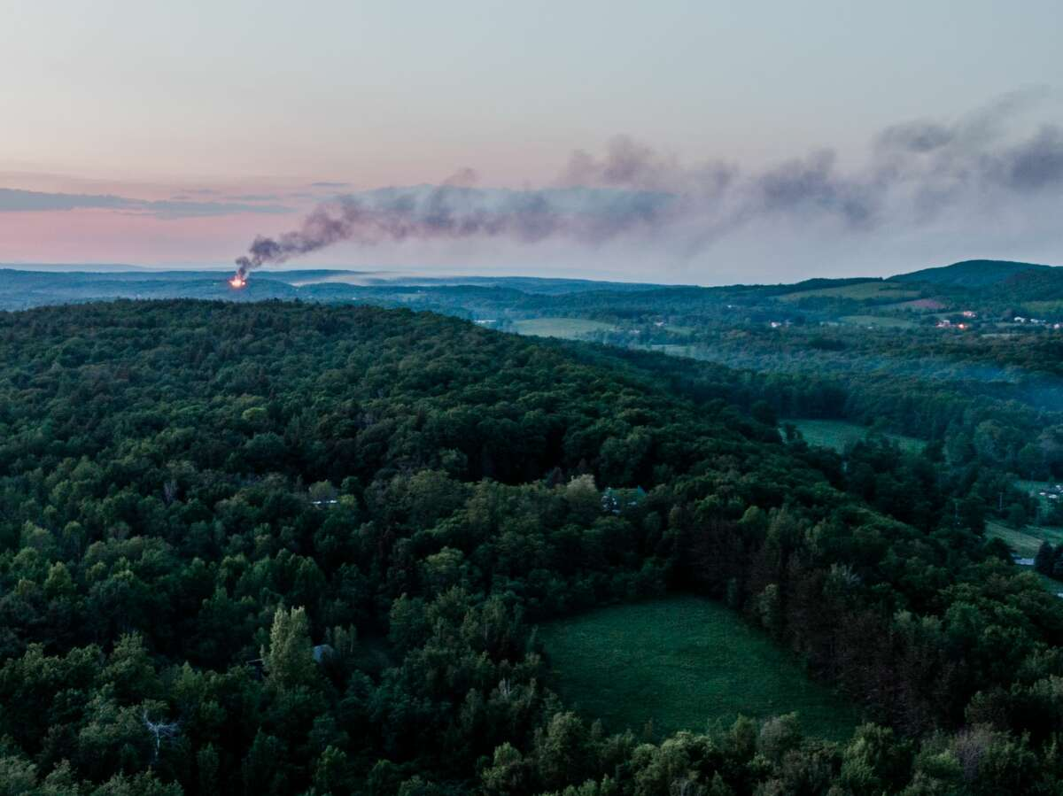 An orange glow from fire and a plume of smoke could be seen from about five miles away from a house explosion in the town of Berne, N.Y. on Friday, June 4, 2021. This image was taken with the use of a drone.