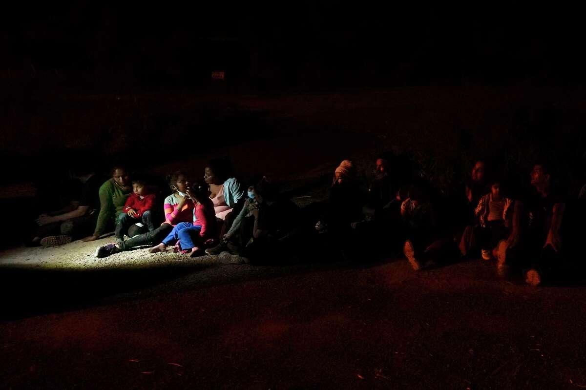 Varios migrantes, principalmente de Honduras y Nicaragua, hacen fila sentados después de entregarse al cruzar la frontera entre Estados Unidos y México, en esta fotografía de archivo del lunes 17 de mayo de 2021 en La Joya, Texas.