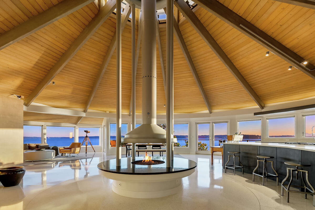 Inside is an open floor plan under a conical roof. A stunning floor-to-ceiling hearth anchors the space.