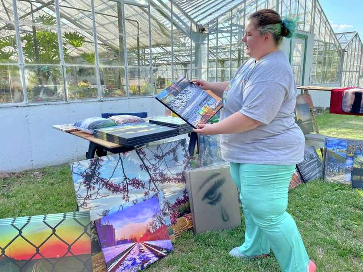 Farmers' market vendor Sara Oestringer holds one of her photographs printed on canvas.