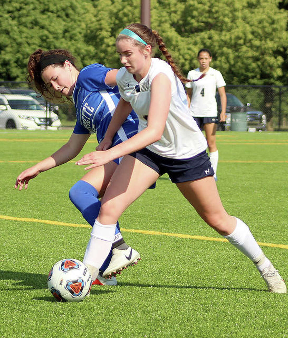 Madelyn Smith of Marquette, left, battles for the ball with McGivney's Adelyn Speight Friday at Gordon Moore Park.