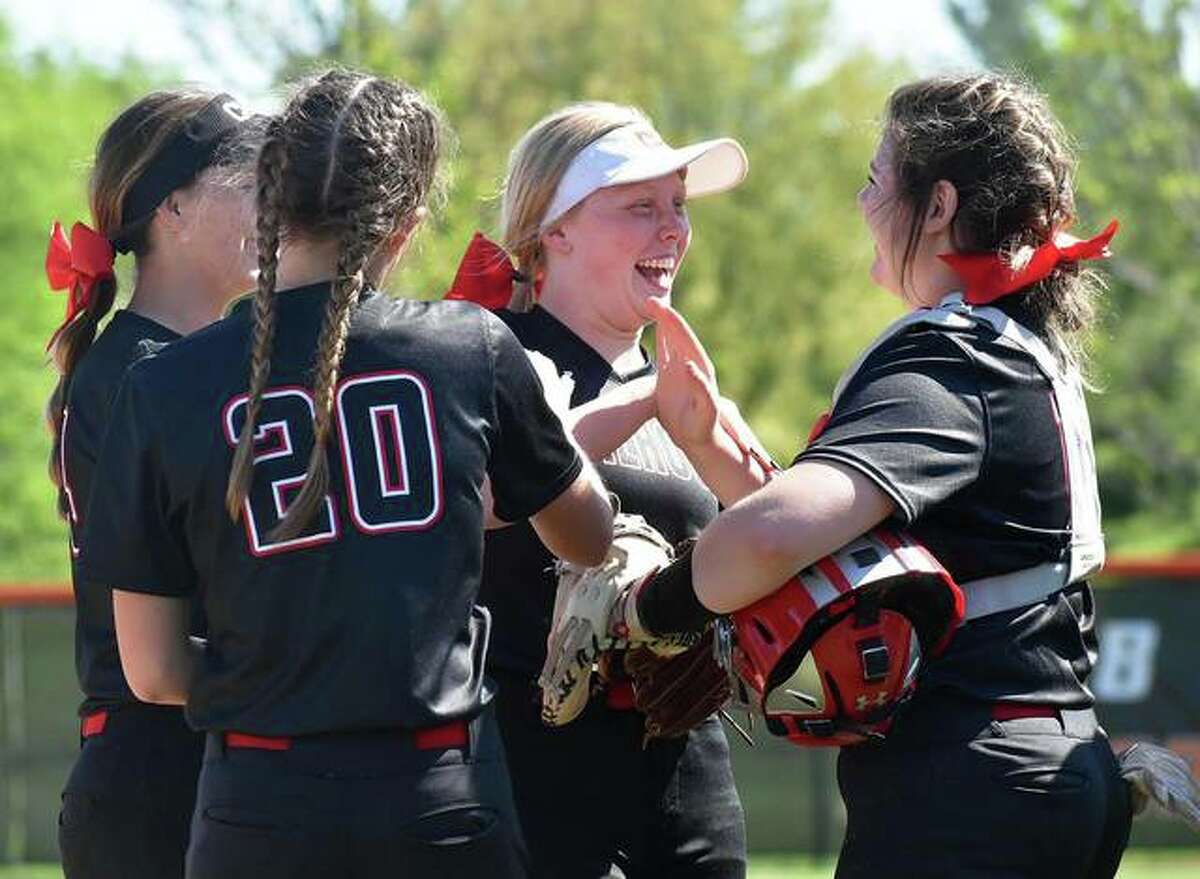 Calhoun outfielder Colleen Schumann (middle) in greeted by teammates after making a running catch in an April 30 game at Edwardsville. Schumann and the Warriors again had reason to smile Friday with Schumann driving in two runs in a five-run third inning that beat Pawnee and delivered a sixth consecutive Class 1A regional title for Calhoun.