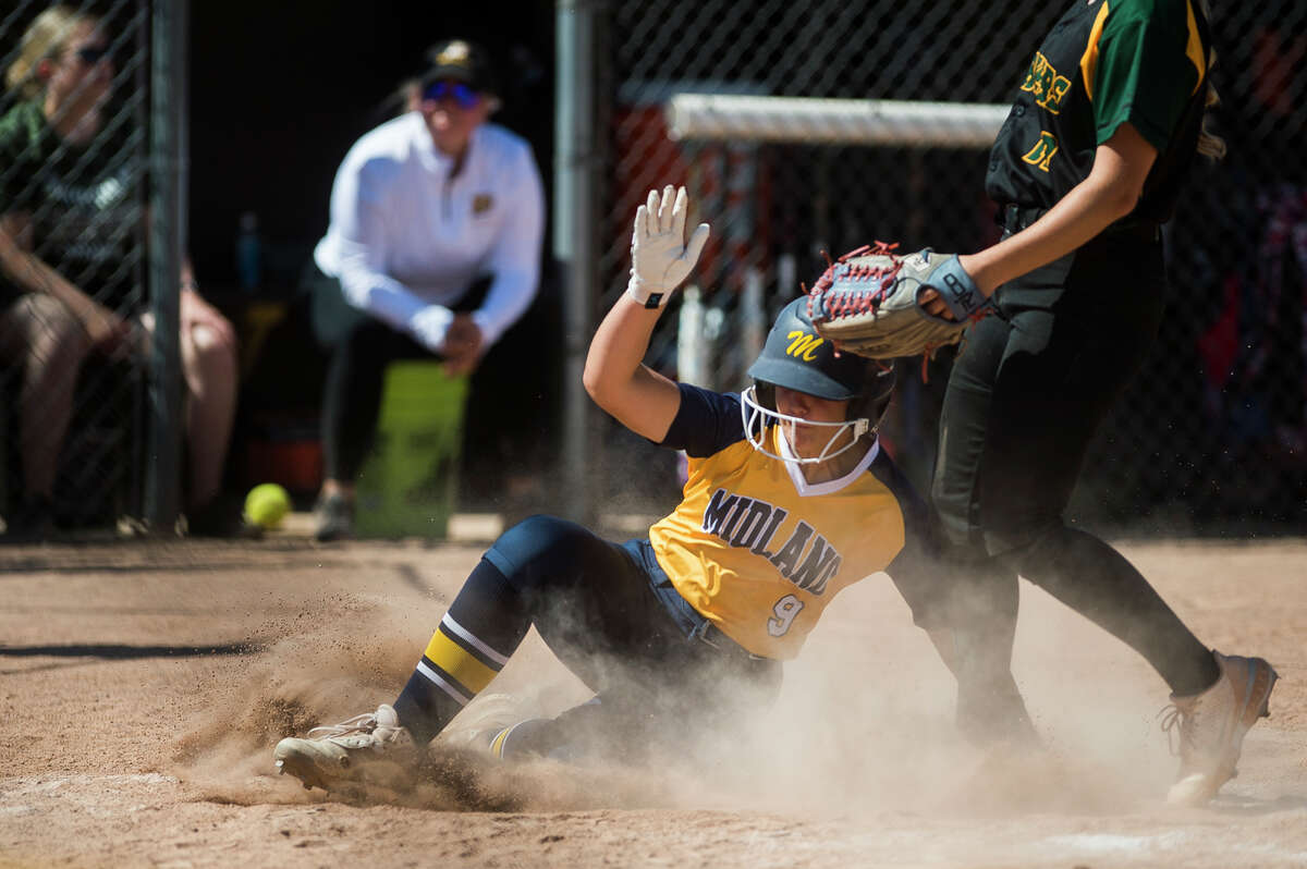 Midland's Grace Schloop slides into home base during the Chemics' game against Dow Saturday, June 5, 2021 at Bay City Western High School. (Katy Kildee/kkildee@mdn.net)