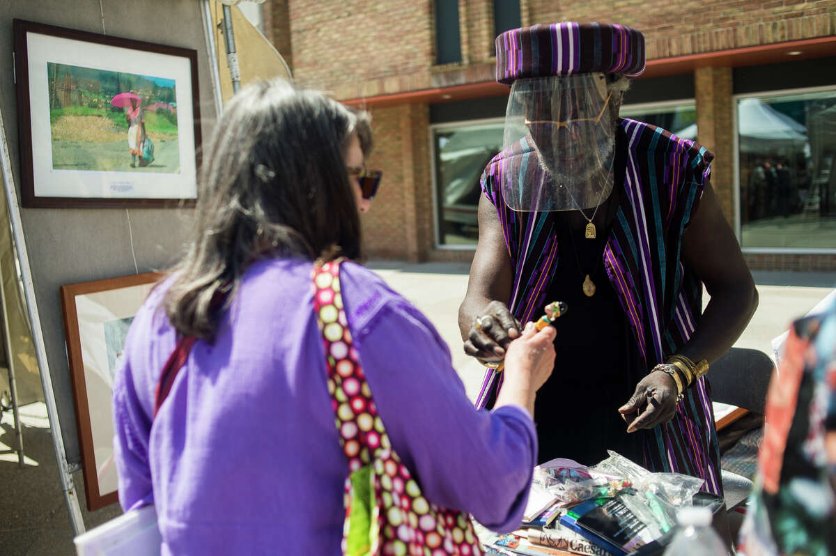 Kenyatta Ray, right, chats with a customer at his booth during the Summer Art Fair Saturday, June 5, 2021 in downtown Midland. (Katy Kildee/kkildee@mdn.net)
